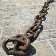 Metallic large chain lies on a rock — Stock Photo