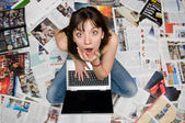 Girl with a laptop sitting on newspapers — Stock Photo