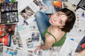 Girl sitting on a newspaper and looks into the camera — Stock Photo