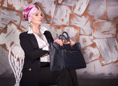Woman in suit sitting on chair with bag — Foto de Stock