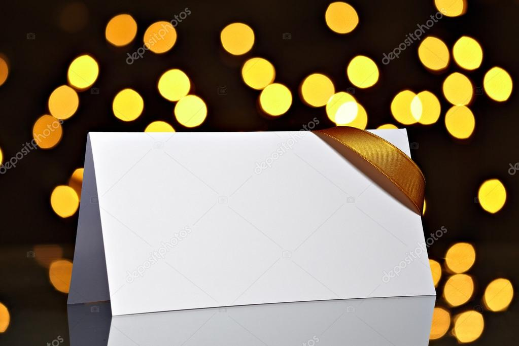 Close up of  card note with ribbon on bright blurred lights background  Stock Photo #13766677
