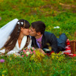 Bride and groom on a picnic in autumn are couple kissing on gree — Stock Photo