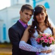 Couple man and woman at wedding next to church on blue backgroun - Stock Photo