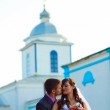 Couple man and woman wedding next church on blue background on s - Stock Photo