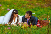 Bride and groom at picnic in autumn are couple on green grass — Stock Photo