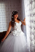 Bride brunette woman standing at the window in the room on the w — Stock Photo