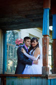 Bride newlyweds and groom standing next to fall old wooden house — Stock Photo