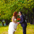 Bride and groom at wedding are in green forest of oak and kiss — Stock Photo