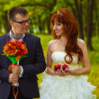 Stock Photo: Bride and groom stand on green background in forest, red haire