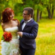 Groom with glasses and red bride at a wedding, walking green for — Stock Photo