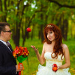 Stock Photo: Bride and groom stand on green background in forest for wedd