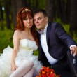 Stock Photo: Redhead bride and groom, wedding in green box, sitting on gr