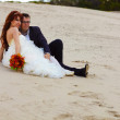 Stock Photo: Newlyweds bride and groom sitting on sand at wedding