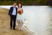 Newlyweds bride and groom go by river — Stock Photo