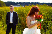 Redhead Bride smelling wedding bouquet on background of green gr — Stock Photo