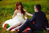 Bride redhead and groom fun laugh, wedding in green field sittin — Stock Photo
