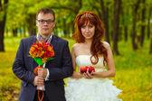 花嫁と花婿 ha 森林、赤の緑の背景の上に立って — ストック写真