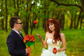 Bride and groom stand on a green background in forest for a wedd — Stock Photo