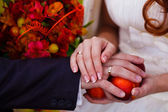 Newlyweds hands rings on wedding bouquet — Stock Photo