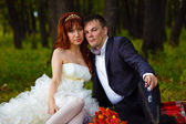 Redhead bride and groom, wedding in green box, sitting on the gr — Stock Photo
