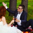 In Russia couple bride and groom communicate sitting on green gr - Lizenzfreies Foto