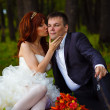Couple bride and groom sitting on green grass, a picnic in woods - Lizenzfreies Foto