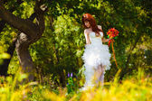Lonely woman in white dress at wedding the bride is tree in a gr — Stock Photo