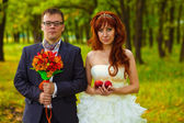 Bride and groom standing on a green background in forest, red ha — Stock Photo