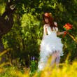 Lonely womin white dress wedding bride is tree in green forest — Stockfoto #15641451