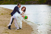 Newly married couple are on the beach at the river, the bride to — Stock Photo