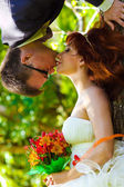 Groom hanging upside down from a tree and kisses the bride unusu — Stock Photo