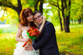 Bride and groom standing in a green forest in summer at the wedd — ストック写真