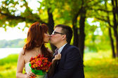 Bride and groom standing in a green forest at the wedding, a man — Stock Photo