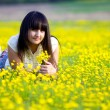 Beautiful brunette girl lying in a field of yellow flowers — Stock Photo