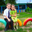 Stock Photo: Boy and girl children sitting outdoors in courtyard of kindergar