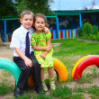 Boy and girl children sitting outdoors in courtyard of kindergar - Стоковая фотография