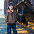 Stock Photo: Boy homeless bum in brown jacket and fur hat and crumpled je