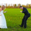 Bride and groom dancing merrily in green field, couple, wedding — Stock Photo