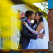Stock Photo: Bride and groom standing at old wooden house and kiss around yel