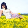 Brunette beautiful girl lying in a field of yellow flowers — Stock Photo