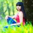 Brunette woman sitting in the grass near the tree in forest — Stock Photo