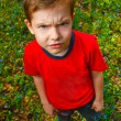 Dissatisfied with evil boy hairy thug in red shirt and jeans, st — Stock Photo