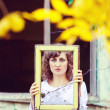 European young woman girl in white dress holding a frame window — Stock Photo