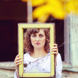 European young woman girl in white dress holding frame window wi — Stock Photo