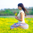 Girl beautiful brunette lying in a field of yellow flowers — Stock Photo