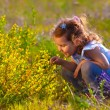 Little baby girl is studying touching look at yellow flower(Cham — Stock Photo