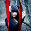 Witch with red ribbons in the woods — Stock Photo