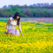 Woman collects yellow flowers in a field in spring — Stock Photo