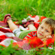 Young man in a red shirt lying in the grass on plaid — Stock Photo