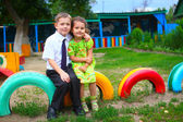 Boy and girl children sitting outdoors in courtyard of kindergar — Stock Photo